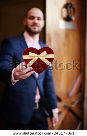 Portrait of attractive caucasian man holding heart shaped Valentine's day gift - stock photo