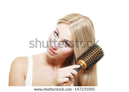 portrait of attractive caucasian smiling blond young brushing her hair isolated on white studio shot  - stock photo