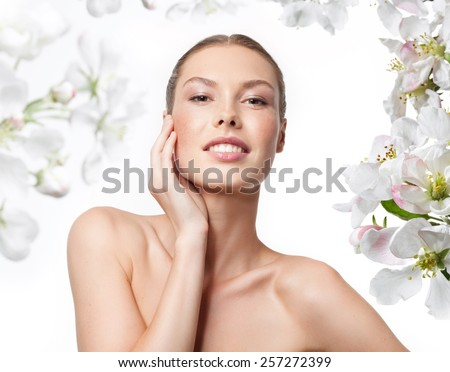 portrait of attractive  caucasian smiling woman blond isolated on white studio shot  toothy smile face skin care hand head and shoulders looking at camera spring flowers - stock photo