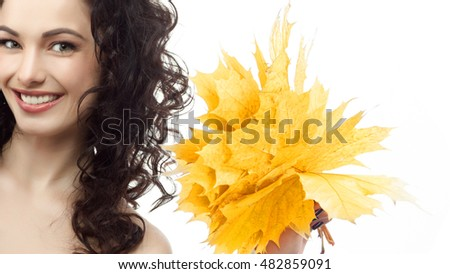 portrait of attractive  caucasian smiling woman brunette isolated on white studio shot head and shoulders face skin hand hair looking at camera hand holding yellow marple autumn leaves