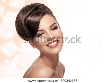 Portrait of attractive caucasian smiling woman brunette with hairstyle, studio shot - stock photo