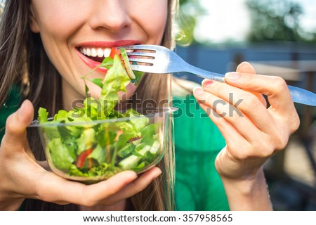 Portrait of attractive caucasian smiling woman eating salad, focus on hand and fork. soft, backlight - stock photo