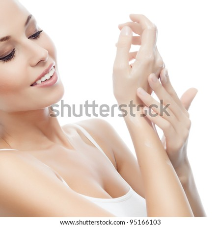 portrait of attractive  caucasian smiling woman isolated on white studio shot applying cream on her hands