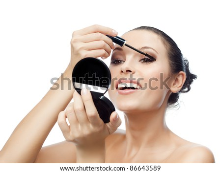 portrait of attractive  caucasian smiling woman isolated on white studio shot applying mascara - stock photo