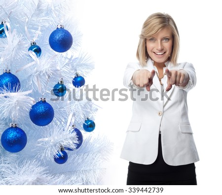 portrait of attractive  caucasian smiling woman isolated on white studio shot looking at camera pointing to new year christmas tree blue balls - stock photo