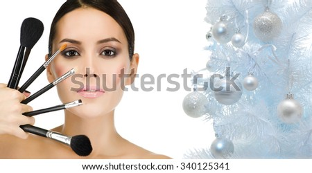 portrait of attractive  caucasian woman brunette isolated on white studio shot face closeup makeup brushes christmas new year tree - stock photo