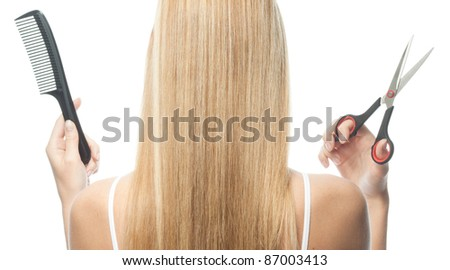 portrait of attractive  caucasian woman  with long blond hair isolated on white studio shot with comb and scissors back