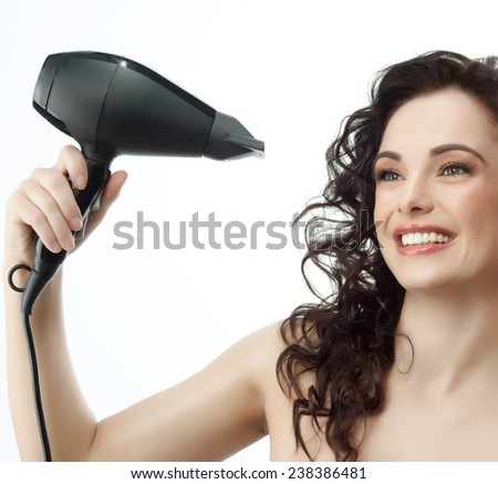 portrait of attractive  caucasian woman  with long  hair brunette isolated on white studio shot making hairstyle with hair drier - stock photo