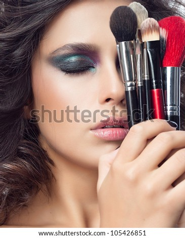 portrait of attractive  caucasian young woman brunette isolated on white studio shot eyes closed face closeup makeup skin hands brushes - stock photo