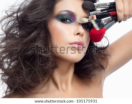 portrait of attractive  caucasian young woman brunette isolated on white studio shot looking at camera face closeup makeup skin eyes brushes hand lips