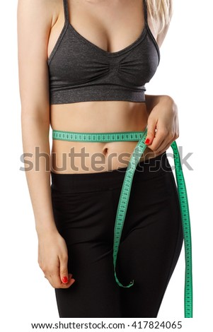 Portrait of attractive cheerful fitness girl measuring her waist with tape in gray top and black leggings with red dumbbells posing over white background isolated  - stock photo