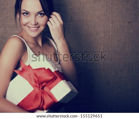 Portrait of attractive cheerful girl in sleeveless sports white shirt holding gift box with red bow over canvas background, toned - stock photo