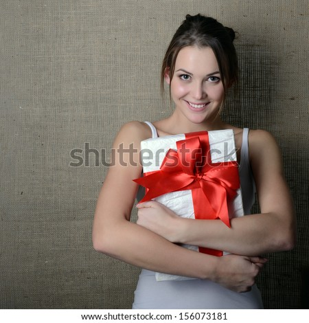Portrait of attractive cheerful girl in sleeveless sports white shirt holding gift box with red bow over canvas background - stock photo