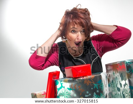 Portrait of attractive cheerful woman  very surprised to discover christmas gifts - stock photo
