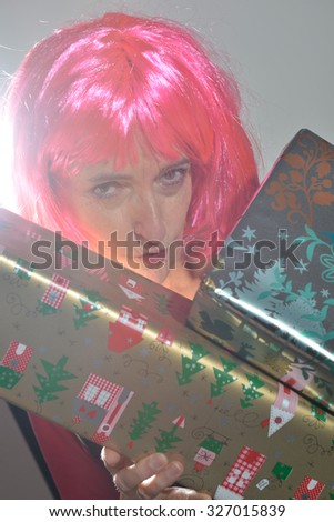 Portrait of attractive cheerful woman with red hair and christmas gifts - stock photo