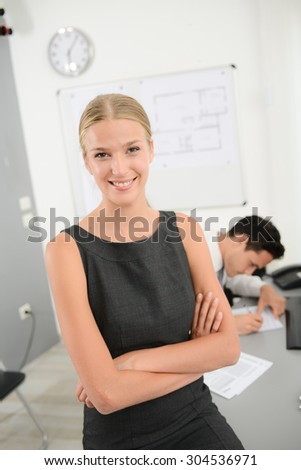 portrait of attractive cheerful young blonde business woman posing in office - stock photo