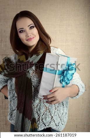 Portrait of attractive cheerful young woman holding gift box with blue bow over canvas background, toned and noise added - stock photo