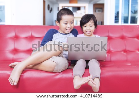 Portrait of attractive children sitting on sofa while using laptop computer to enjoy movie at home - stock photo