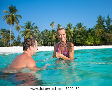Portrait of attractive couple having fan on the tropical beach - stock photo