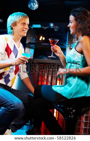 Portrait of attractive couple looking at each other and chatting in the bar - stock photo