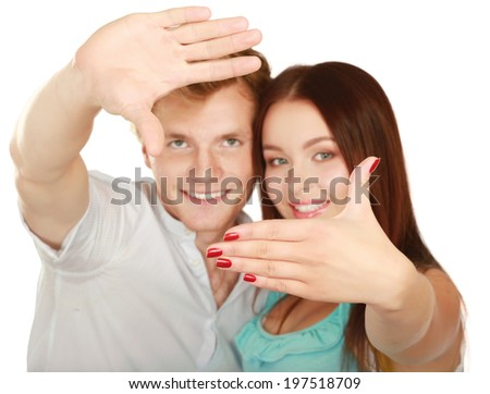 Portrait of attractive couple making frame from fingers and looking through it at camera - stock photo