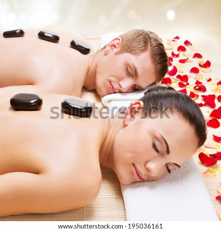 Portrait of attractive couple relaxing in spa salon with hot stones on body.  - stock photo