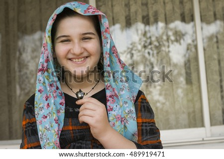 Portrait of Attractive Cute Muslim Girl Looking directly at the Camera. Positive Human Emotion Facial Expression Body Language. Funny Girl Touching Heart Shape Necklace