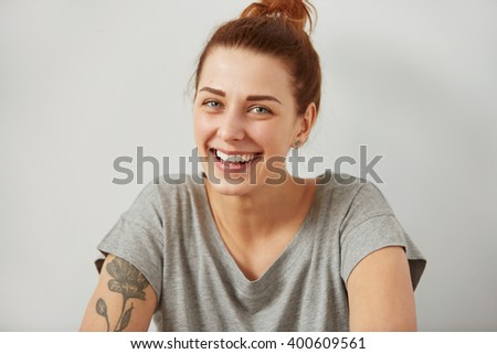 Portrait of attractive cute woman laughing or smiling over gray background. Looking at the camera. Positive human emotion facial expression body language. Funny girl - stock photo