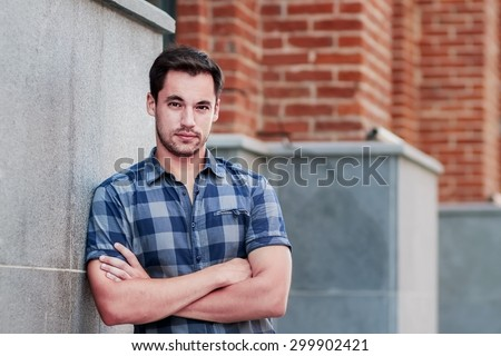 Portrait of attractive dark-haired young man standing crossing arms against an urban background. Image with selective focus - stock photo