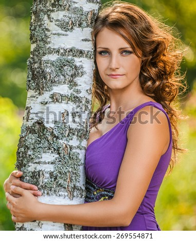 Portrait of attractive dark-haired young woman wearing violet t-shirt near birch tree at summer green park. - stock photo