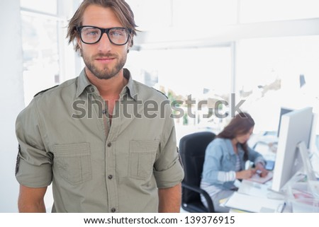Portrait of attractive editor with colleague working behind - stock photo