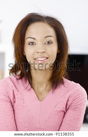 Portrait of attractive ethnic girl in pink, smiling at camera.? - stock photo