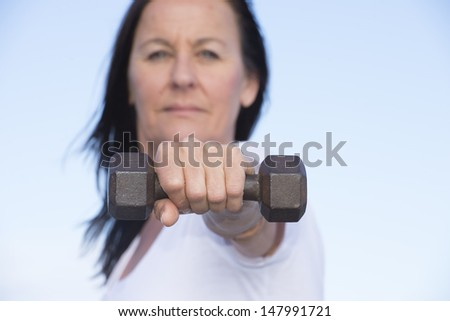 Portrait of attractive exercising mature woman in blurred background with stretched out arm with weight in focus, confident and determined, active and healthy lifestyle, with sky as copy space. - stock photo