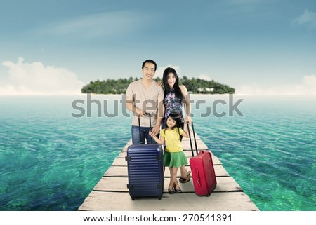 Portrait of attractive family arriving at resort and standing at resort bridge with their luggage - stock photo
