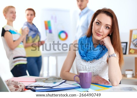 Portrait of attractive female  designer sittin on thesk  in office - stock photo