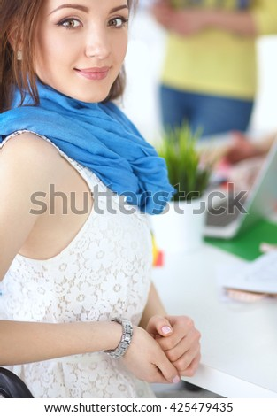 Portrait of attractive female  designer sitting on desk  in office - stock photo