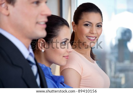 Portrait of attractive female executive standing with her colleagues - stock photo