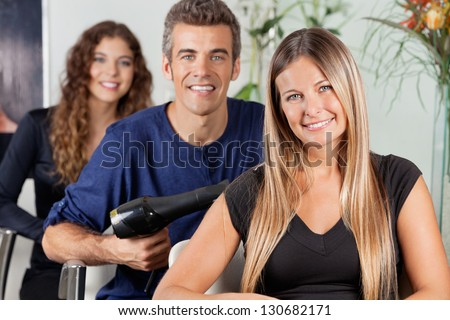 Portrait of attractive female hairdresser sitting with colleagues at beauty parlor - stock photo