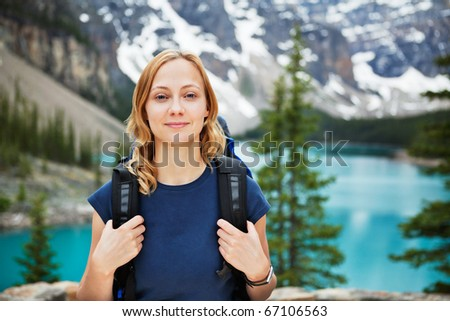 Portrait of attractive female hiker with her backpack against scenic view - stock photo