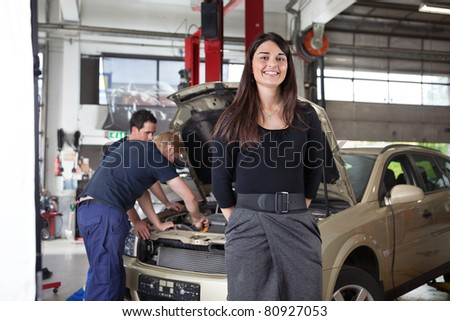 Portrait of attractive female in garage while people working in background - stock photo