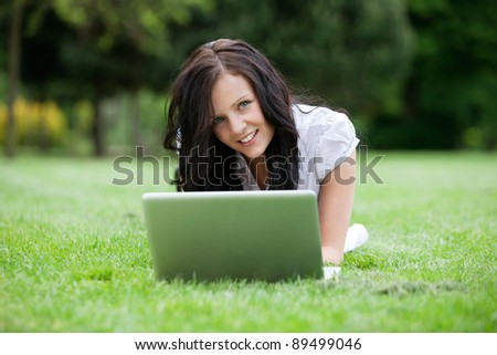 Portrait of attractive female lying on grass using laptop