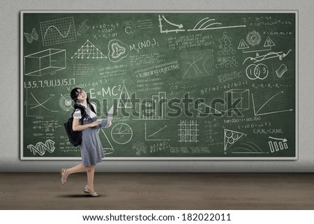 Portrait of attractive female student posing while holding a laptop computer. shoot at class - stock photo