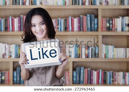 Portrait of attractive female student showing a LIKE icon with a tablet screen in the library - stock photo
