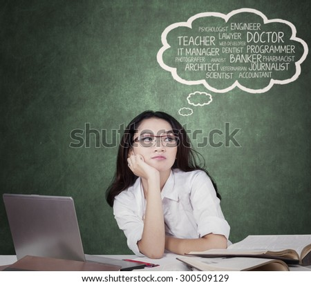 Portrait of attractive female student with long hair, daydreaming about future jobs in the class with books and laptop on the table - stock photo