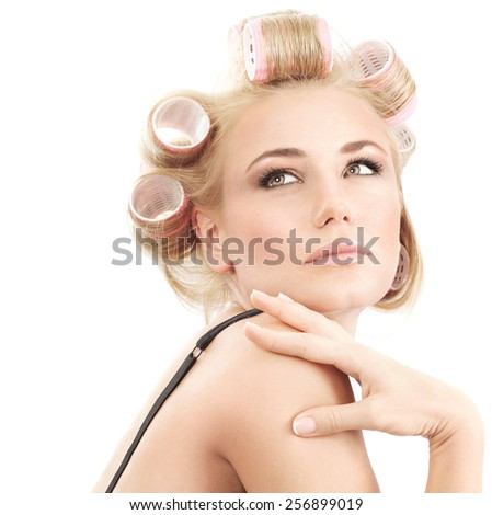 Portrait of attractive female with curlers on hair isolated on white background, making stylish hairdo, fashion and beauty concept - stock photo