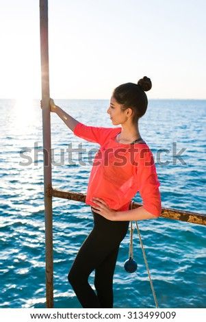 Portrait of attractive fit female rest after physical exercise outdoors while standing on the pier in sunny summer day, young runner woman taking break after run while enjoying seashore scenery view - stock photo