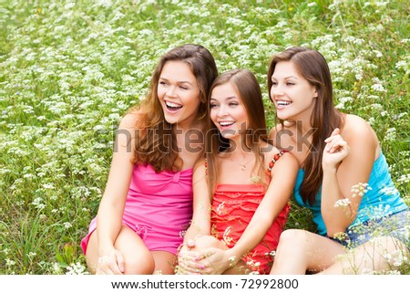 portrait of attractive friends sitting down on grass - stock photo