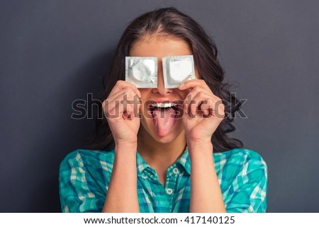 Portrait of attractive girl covering eyes with condoms and showing her tongue, against dark background - stock photo