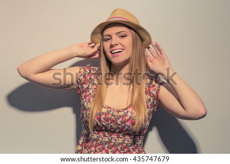Portrait of attractive girl in summer clothes looking at camera and smiling, against gray background - stock photo