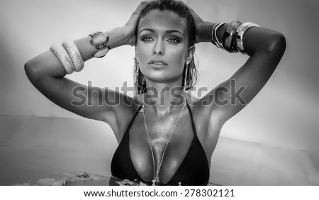 Portrait of attractive girl relaxing, sunbathing. Woman wearing jewelry. - stock photo